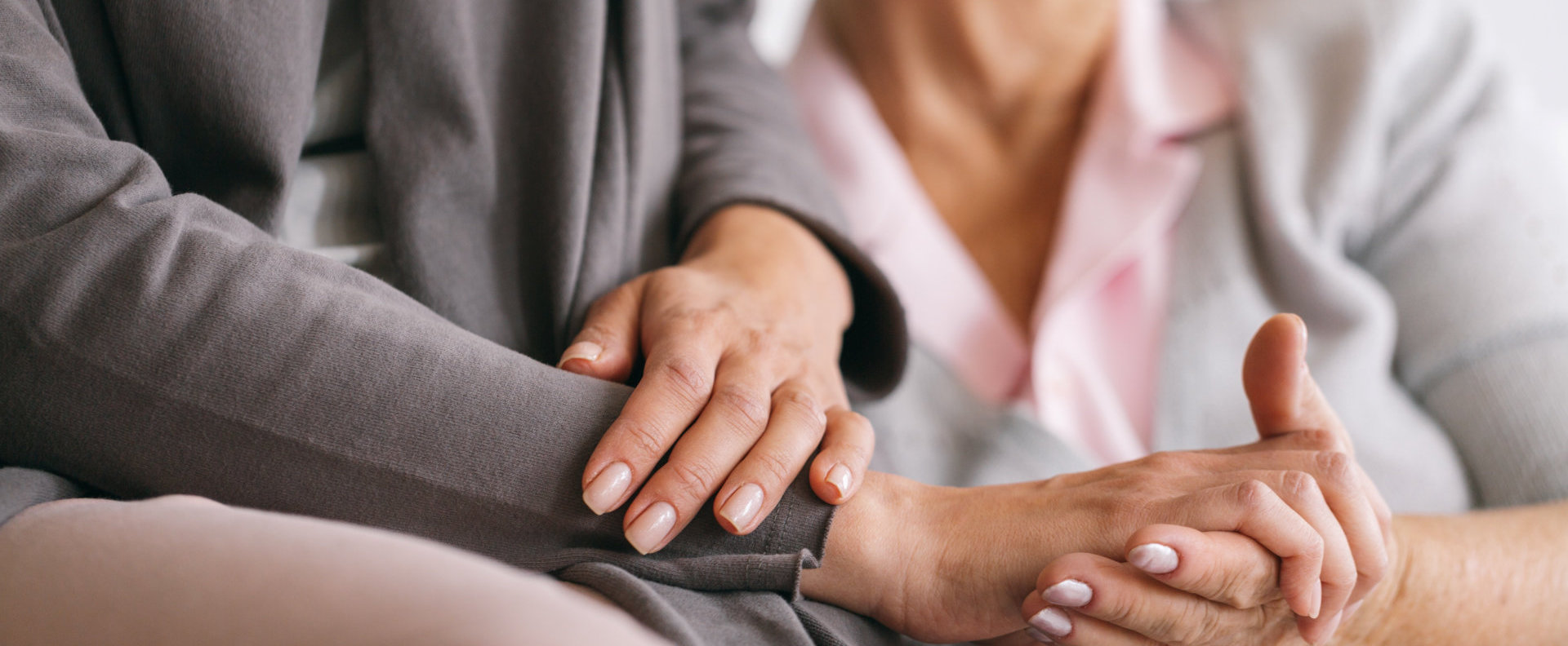 Close up of older woman`s and caregiver`s hands