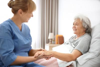 caregiver holding senior woman hands