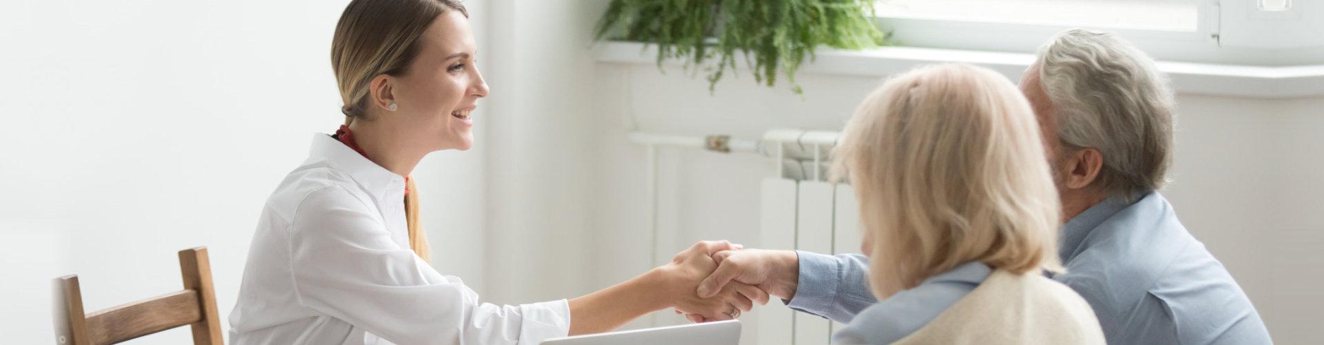 Smiling female lawyer, real estate agent or financial advisor handshaking older senior couple