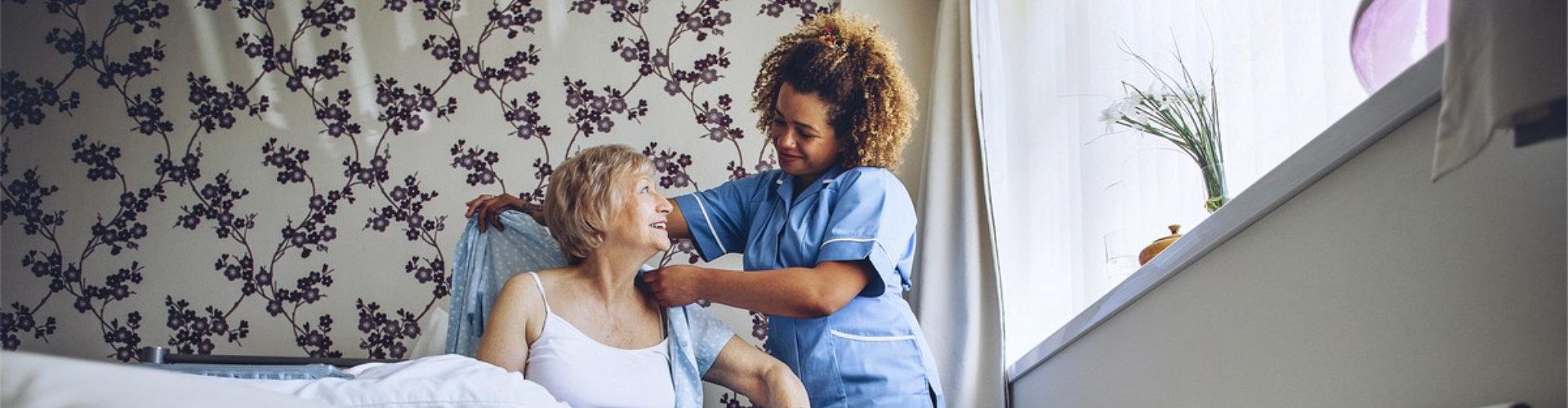 caregiver assisting senior woman to dress up